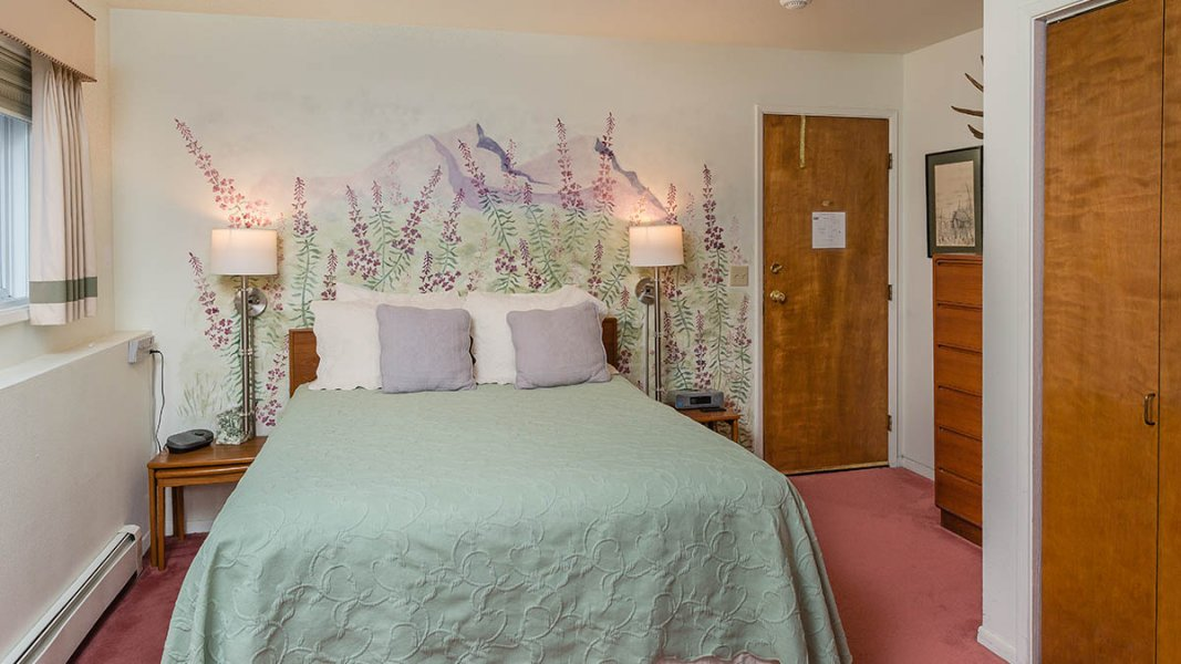 Queen bed with green spread by wall painted with flowers, salmon carpet, stands with lamps, dresser by entrance door.