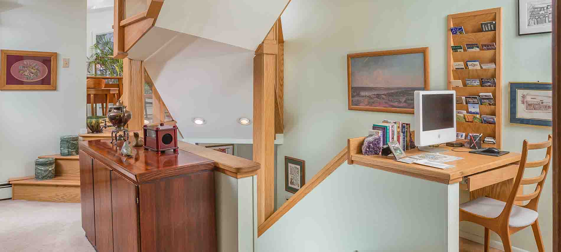 Light green room at top of stairs; walnut counter top with computer; walnut rack card display built into wall