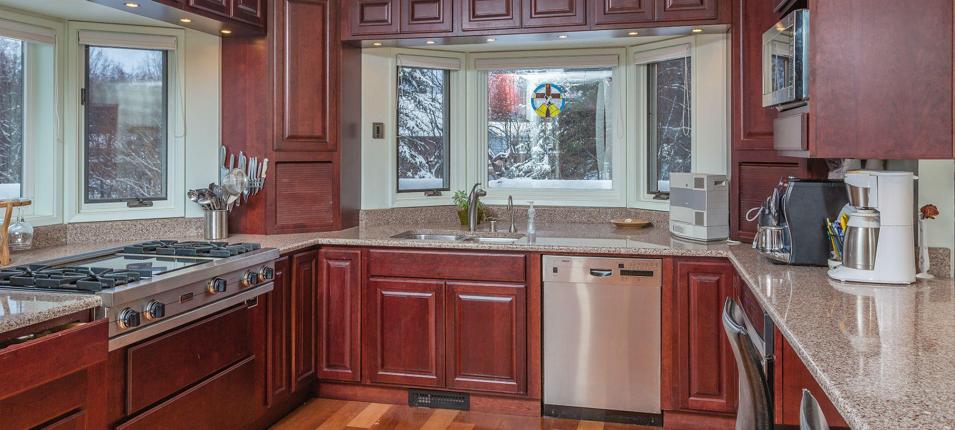 Kitchen with stainless steel appliances and cherry cabinets on all sides, bay windows, marble counters, wood floor.