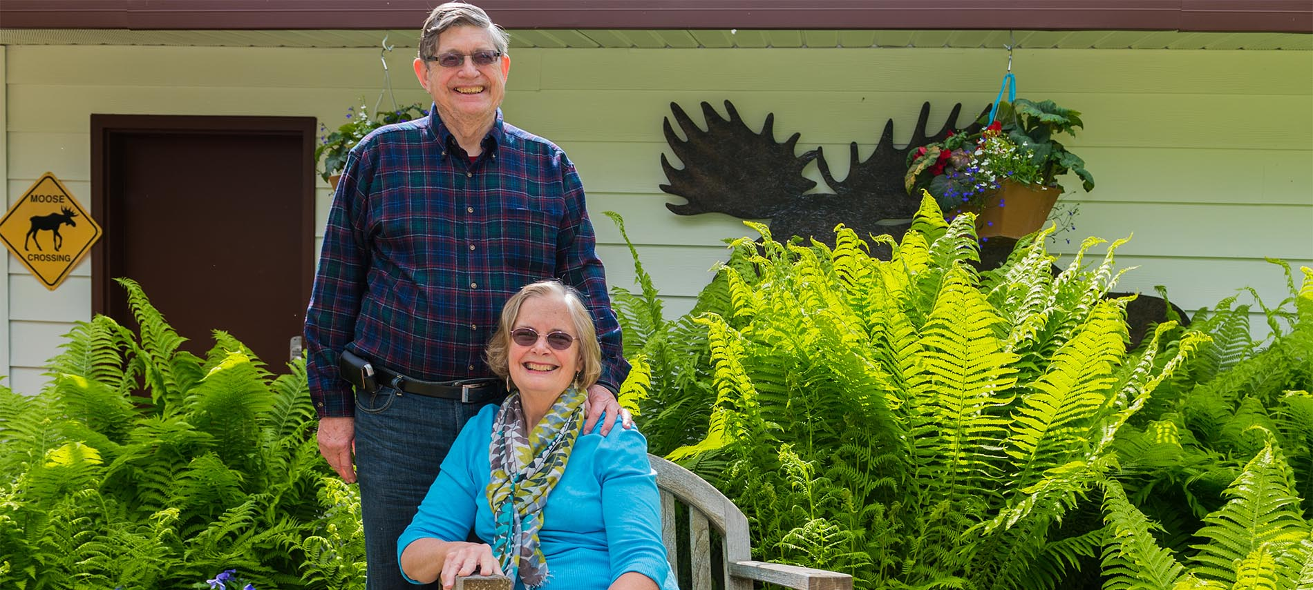 Craig standing next to Caroline seated in garden with lush green ferns and moose silhouette in background