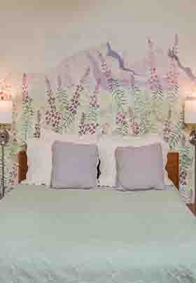 Wall scene above queen bed shows fireweed blooms on purple mountain peaks; wall lamps on each side of bed