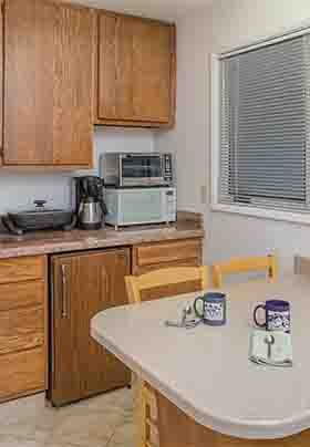 Wall of walnut kitchen cabinets; white sink, microwave, refrigerator, toaster oven, coffee maker; counter with four chairs