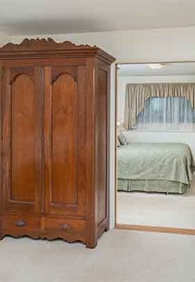 Antique walnut armoire; green granite counter with microwave and toaster oven; looking into suite's other room with queen bed