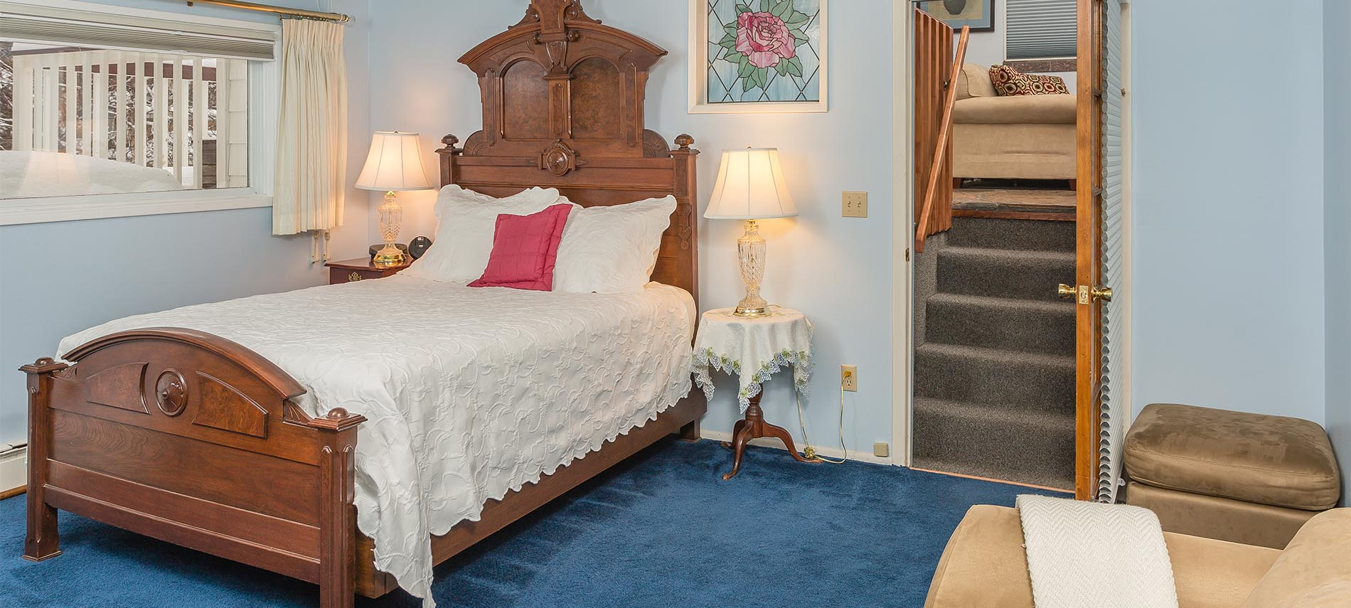 Antique queen bed with white spread; beige chair and ottoman; deep blue carpet; stairs leading to upper room with sofa