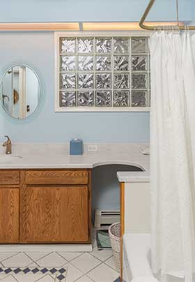 Blue bathroom with shower in tub, white sink; glass brick window; white tile floor with blue diamond inlay