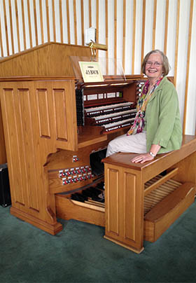 Caroline in green jacket with floral scarf seated on organ bench