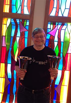 Craig in black F flat=mc squared shirt.; holding two handbells; stained glass window background