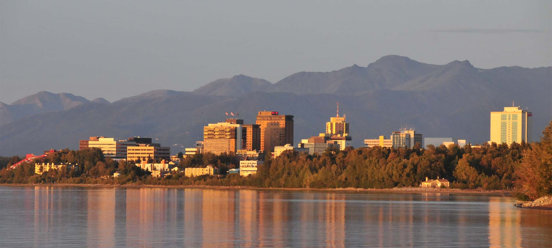 Snow-free mountain background with sun-drenched tall city buildings reflected in foreground's lake; fall's orange tinged trees surround lake