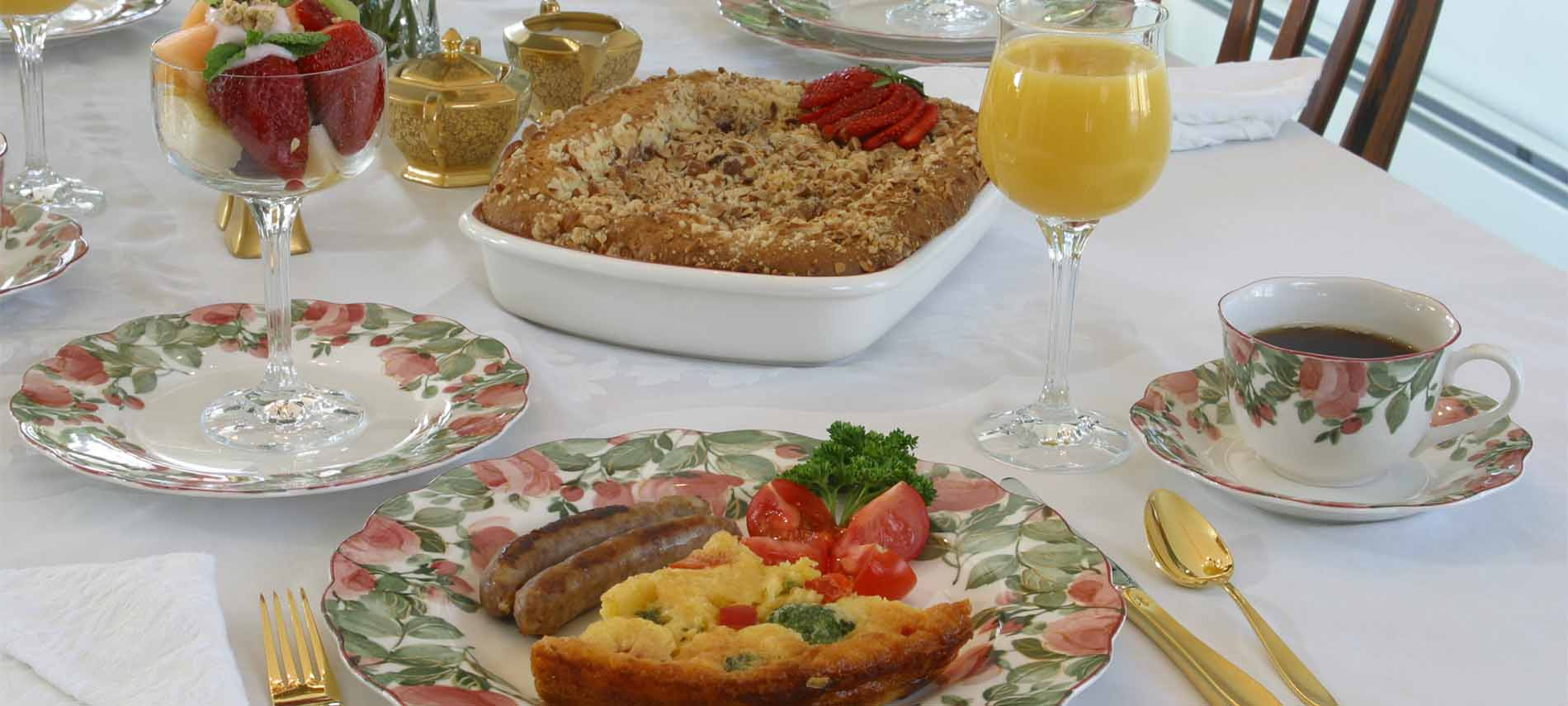 Quiche slice with sausages, tomato, parsley on plate with rose, green foliage pattern; cup of coffee; colorful fruits in goblet
