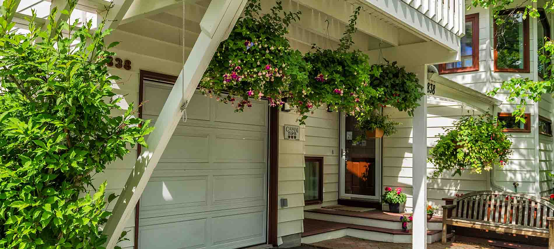 White upper deck with hanging pink fuchsia hanging baskets leads to front entry's deck with garden bench